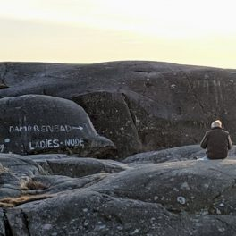 "Man eating sandwiches next to a sign painted on the rocks: ""Ladies nude"""