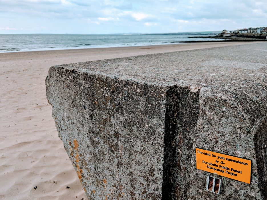 "Pencil sharpener attached to the sea wall at the beach, labelled: ""Provided for your convenience by the Portobello Public Pencil Sharpening Project"""