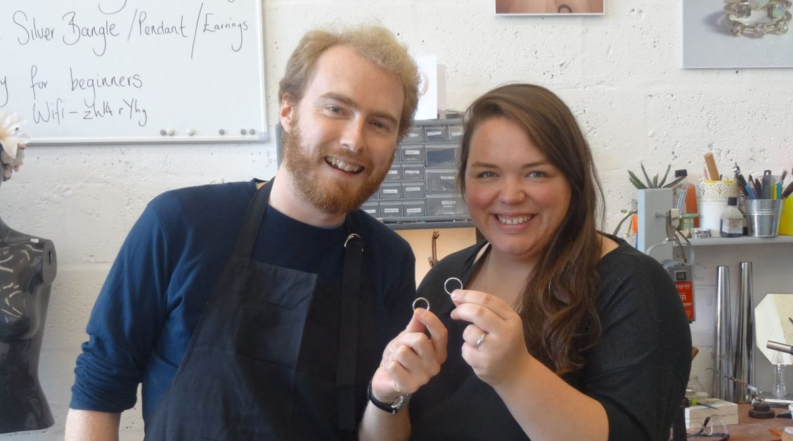 Me and Alex holding our wedding rings in the workshop