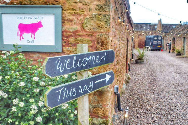 'Welcome - This way' signs at the entrance to the Cow Shed
