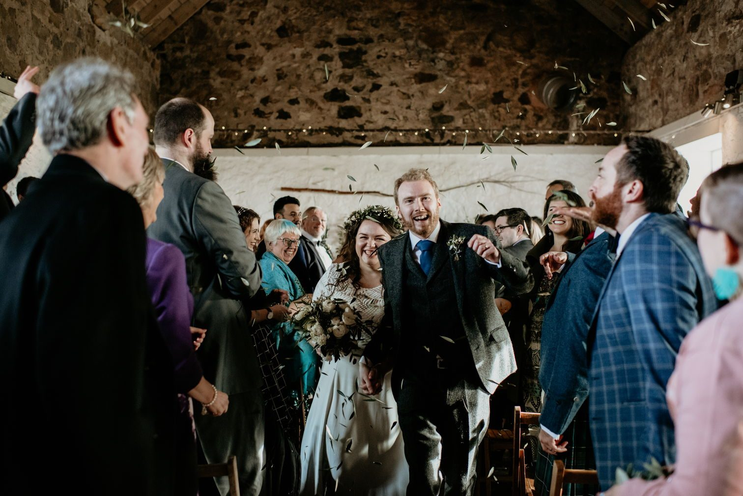 Alex and me walking back up the aisle, with people throwing olive leaves as confetti