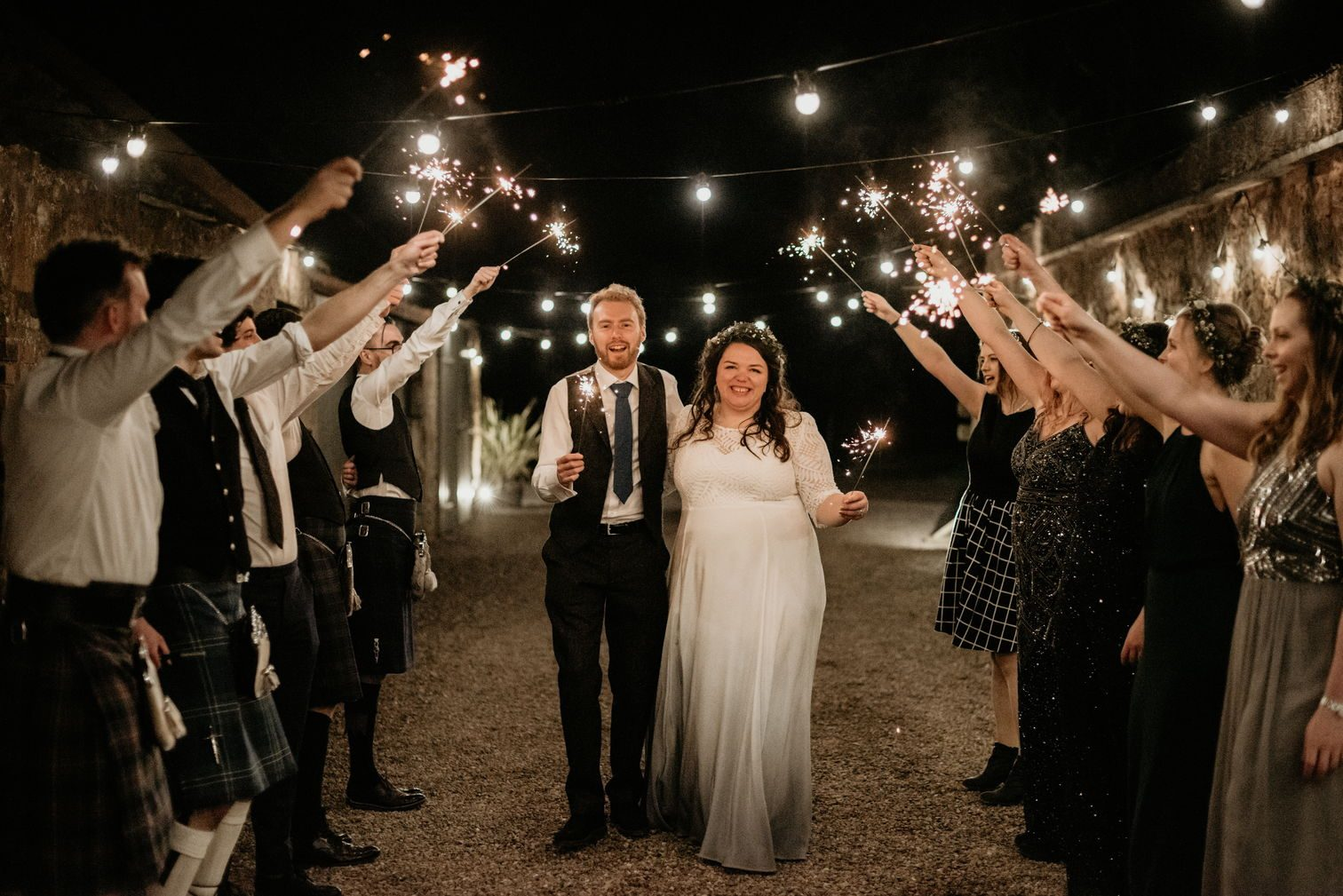 Me and Alex, groomsmen and bridesmaids, celebrating with sparklers