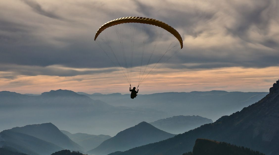 Person in a parachute over hills