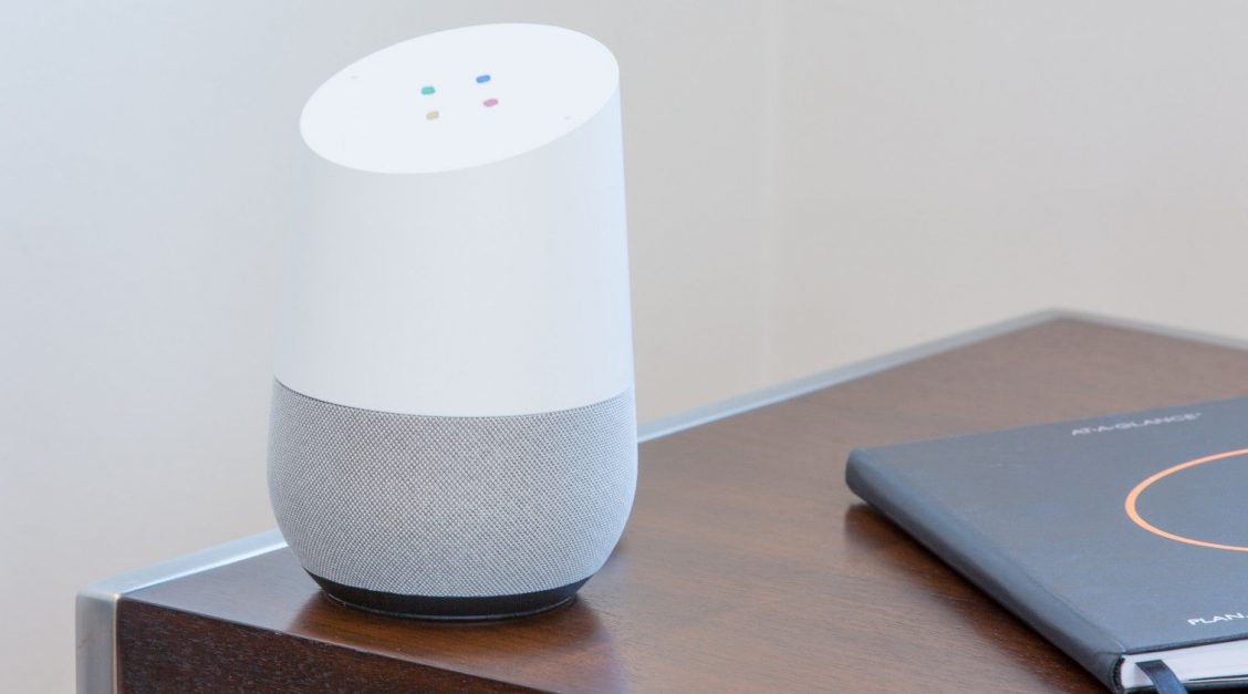 Google Home device on a table next to a book