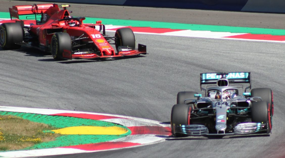 Charles Leclerc behind Lewis Hamilton on the racetrack