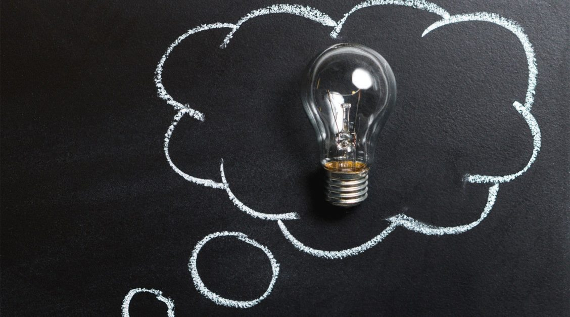 Blackboard with a thought cloud containing a light bulb drawn on it