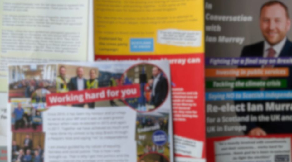Blurred-out photo of Labour leaflets that don't mention Labour