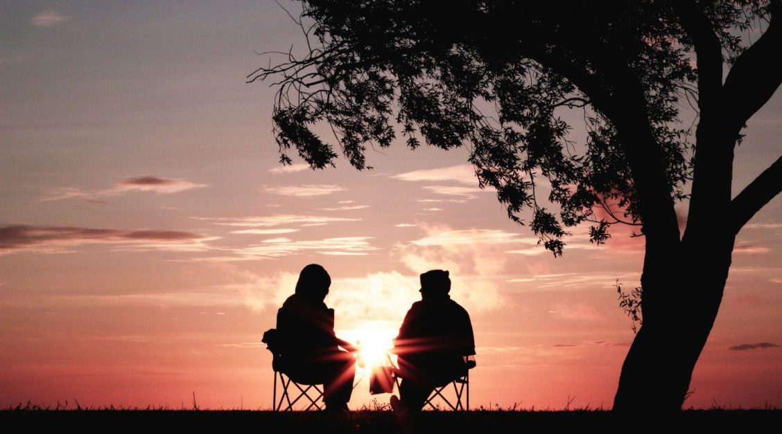 Two people talking at sunset