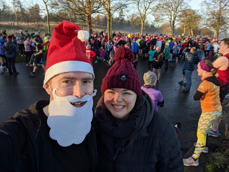 Me wearing a santa hat and beard at Cramond parkrun with Alex