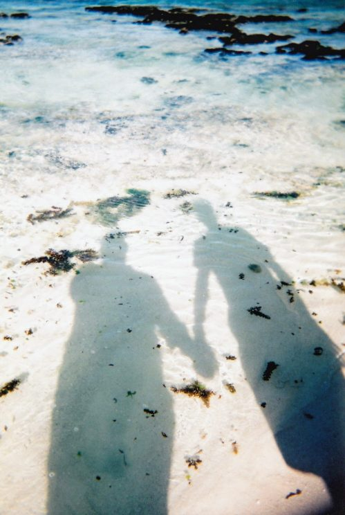 Shadows of Alex and me holding hands on the beach (taken on the disposable camera)