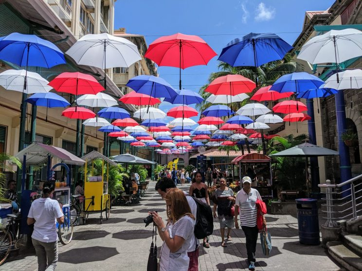 Blue, white and red parasols suspended above a street in Port Louis