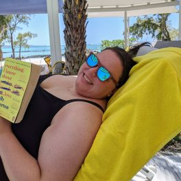 Alex reading her book by the pool
