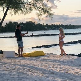 Another man taking a photo of another woman on the beach