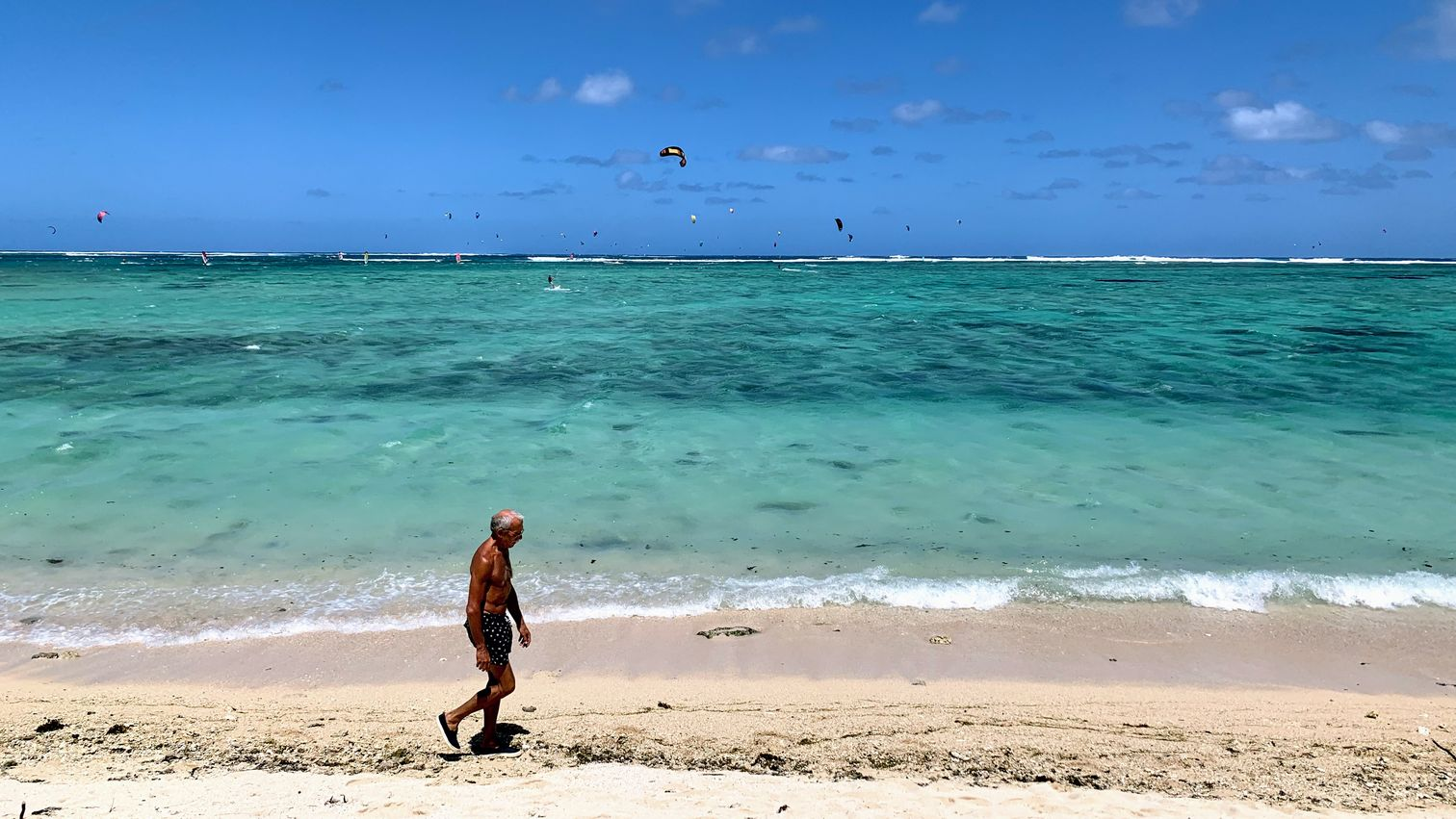 A man walking across the beach at Le Morne