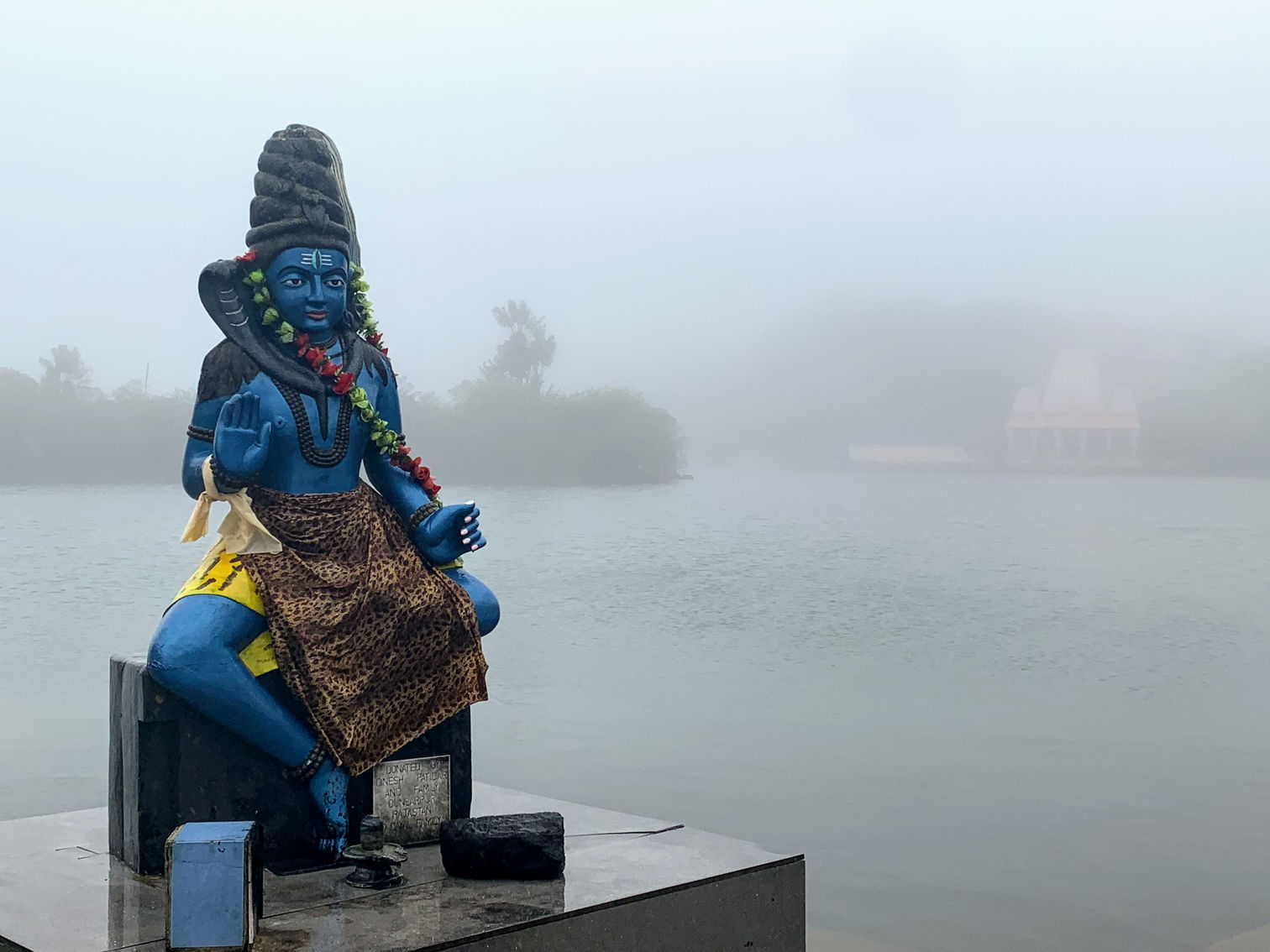 Statue of a Hindu deity at Grand Bassin in heavy rain conditions