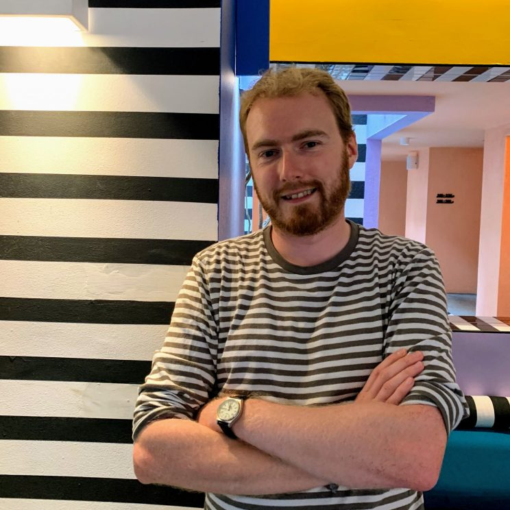 Me wearing a stripy t-shirt next to the stripy interior design of the hotel lobby