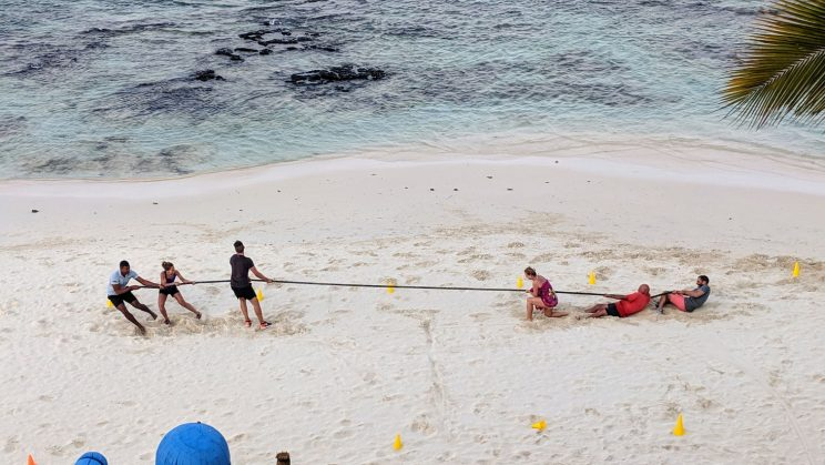 People playing tug of war on the beach