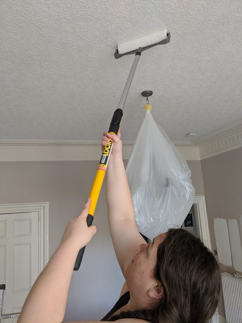 Alex using a long roller to paint the ceiling