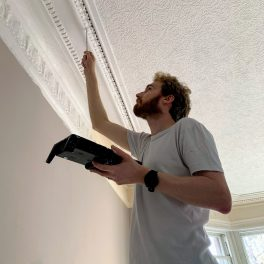 Me painting the intricate bits of the cornice with a tiny paintbrush