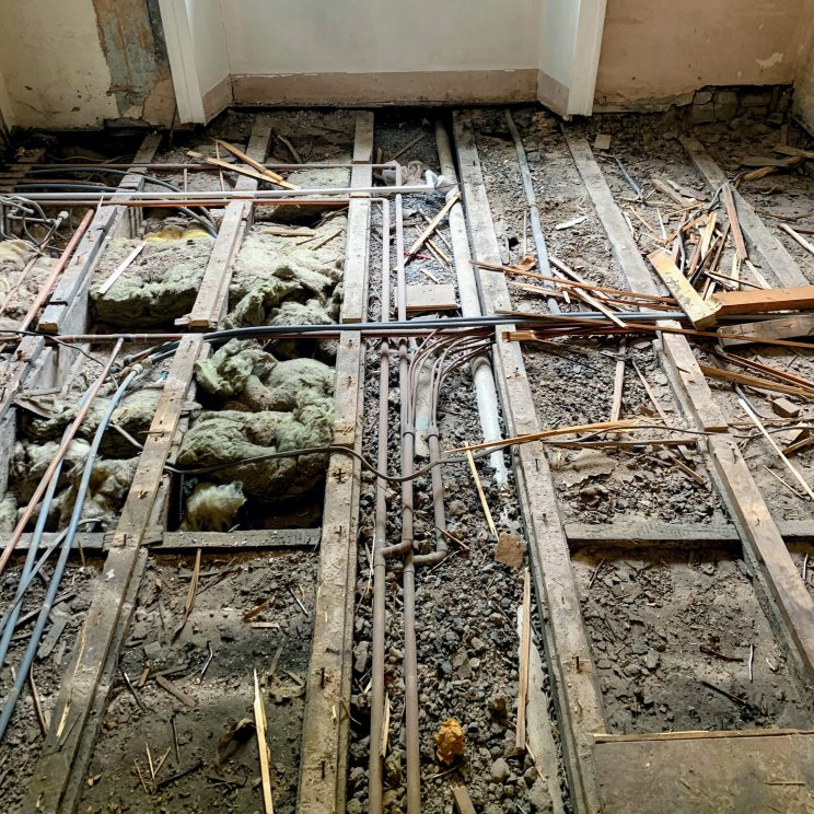 A floor without the floorboards, with deafening and pipes visible