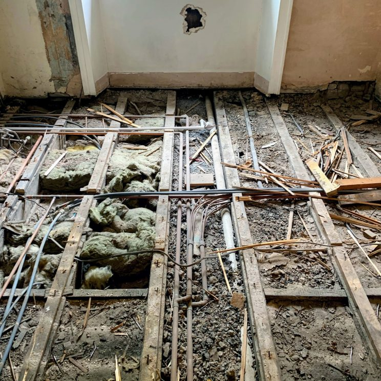 Floorboards raised, revealing the joists and deafening
