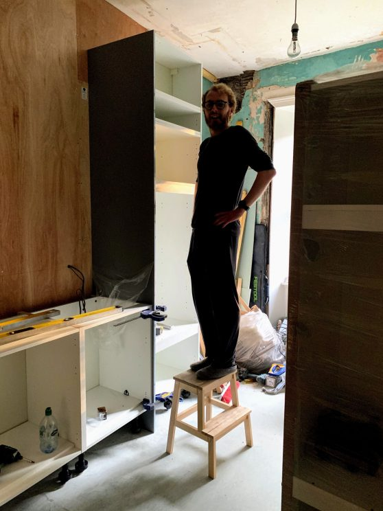 Standing on a step stool to reach the top cupboard