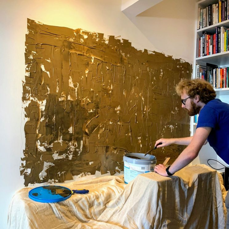 Applying gross adhesive to the study wall